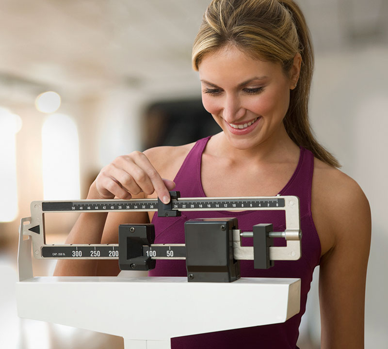 Woman Weighing Herself - hCG Weight Loss